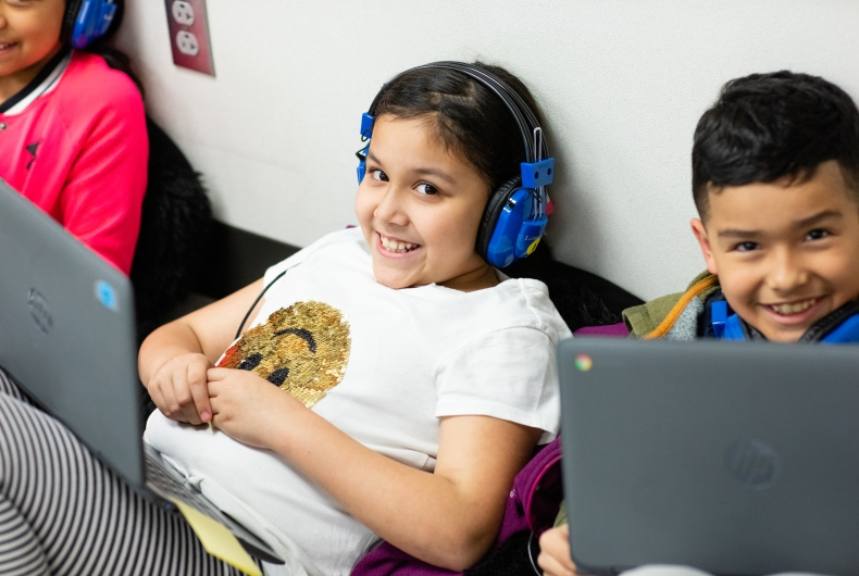 A student wearing headphones with a laptop in front of her smiles at the camera. A student next to her with a laptop also smiles for the camera.